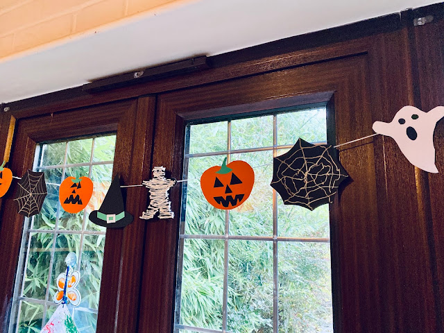 Patio doors with a string of halloween shapes hung up in front of it. The halloween bunting is made of a witches hat, pumpkins, ghosts, spiders web and mummies