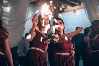 Damas de honor en la fiesta llevando copas y bengalas en la mano
