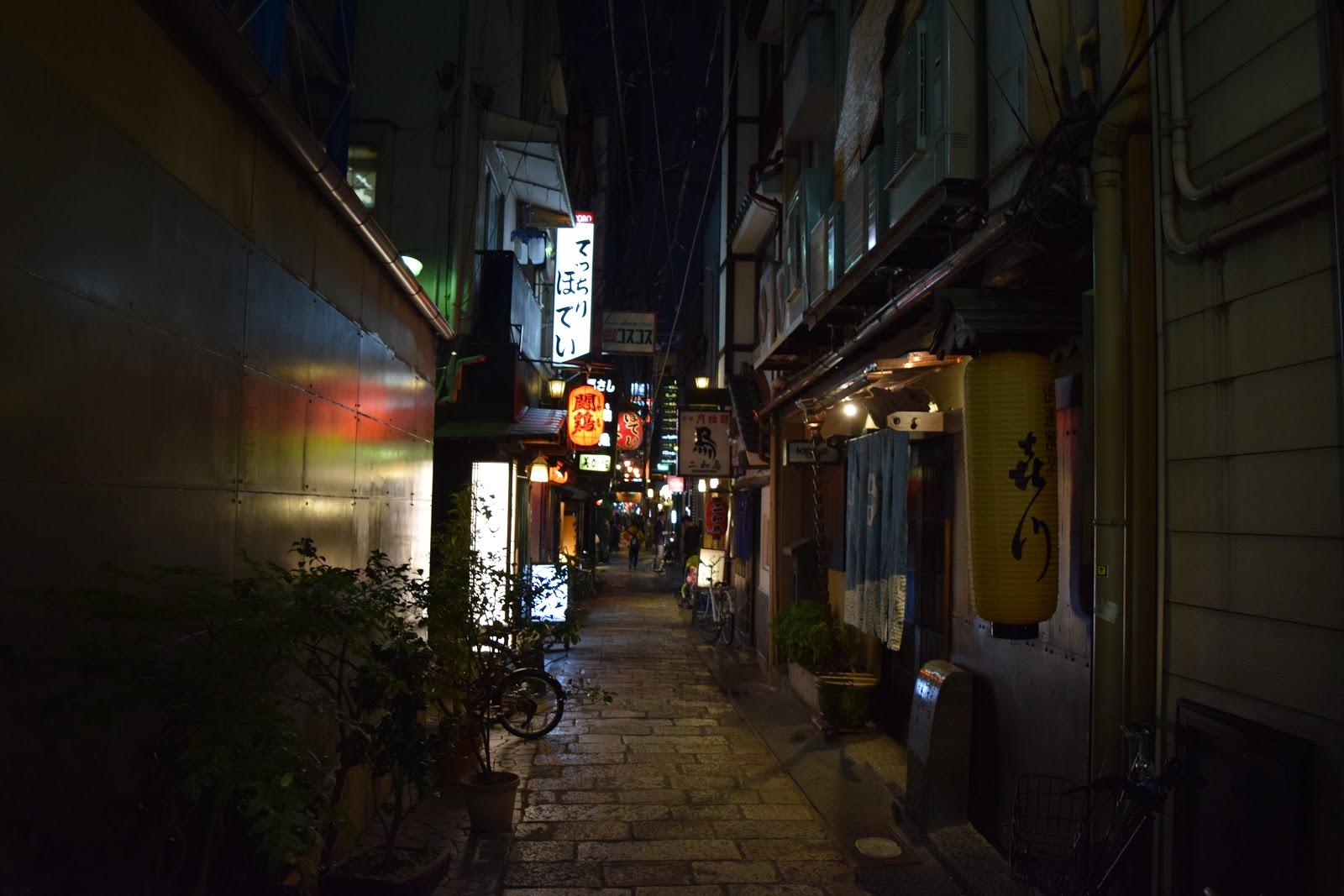 Namba, Osaka side street at night with lanterns, neon lights and bicycles