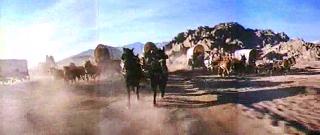 Otro fotograma de La conquista del Oeste. La imagen muestra varias carrozas tirada por caballos a toda velocidad sobre un camino de tierra