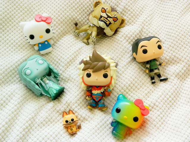 A photograph of several funko pop vinyl figures: a rainbow hello kitty, a classic hello kitty with a red hair bow, Galadriel from LOTRs, a little boy and his cat sidekick, and Mulan as Ping
