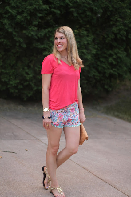 coral top, printed pom pom shorts, gold sandals, straw clutch