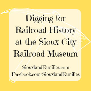 """a white pickax is on a yellow background. in foreground, the words """"Digging for Railroad History at the Sioux City Railroad Museum"""""""