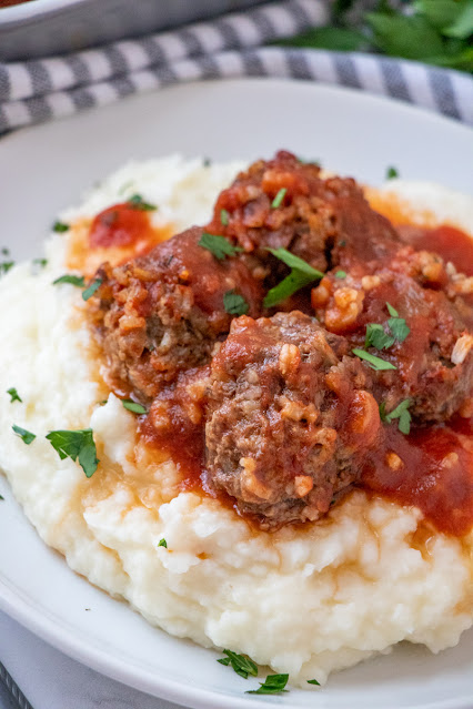 meatballs and sauce over mashed potatoes on a plate.