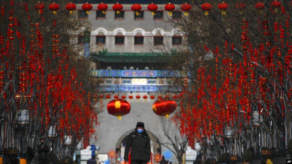 Un guardia de seguridad con mascarilla camina por la calle Quanmen, normalmente popular entre los turistas pero que aparece casi vacía, en Beijing, el domingo 16 de febrero de 2020 / AP Foto/Andy Wong