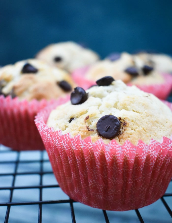 Close up of choc chip muffins in pink cases on a wire cooling rack