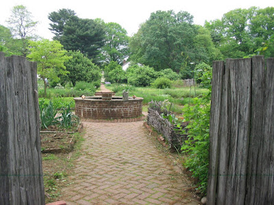 Wooden gates open onto a garden with a brick path leading to a brick-enclosed well in the middle. Plants grow in raised beds and along fence lines