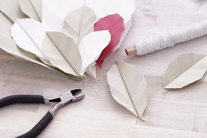 Gefaltete Origamiblätter mit Zange und Draht