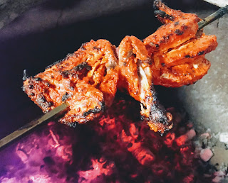 Shewering Tandoori chicken pieces cooking in Ovalclay Tandoor for Tandoori chicken recipe