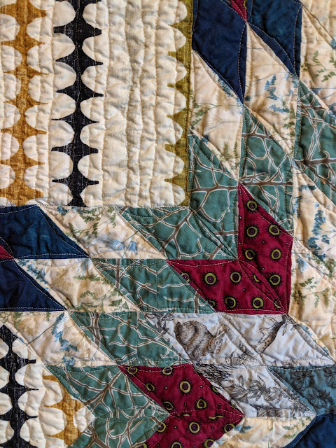 The Lone Star is quilted with FMQ orange peels and the background is quilted with organic parallel lines.