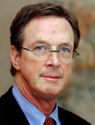Foto de Michael Crichton, persona caucásica entrada en años, con gafas y ojos azules.