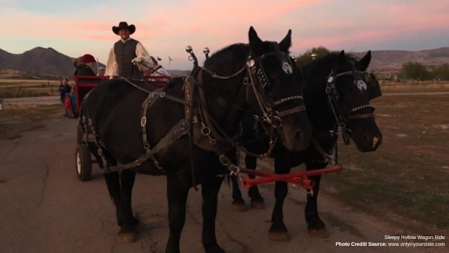 a red carriage pulled by two black horses