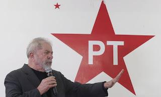 Lula discursando com o símbolo do PT atrás