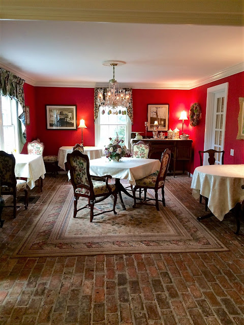 dining room with red walls, and four tables with ivory tablecloths set beneath bright windows