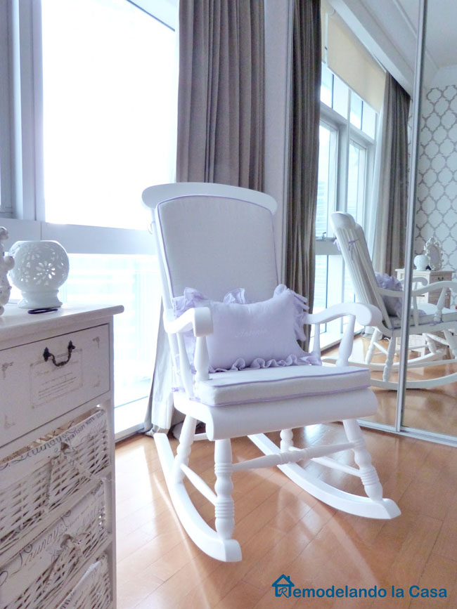 rocking chair in baby girl nursery with mirror on the back