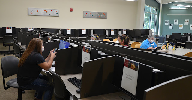 Students spread out at different computers in the library