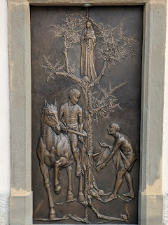The bronze door of the Chiesa di San Martino della Pigrizia showing the saint giving half his cloak to a beggar.