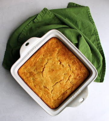 square casserole dish of corn casserole fresh from the oven