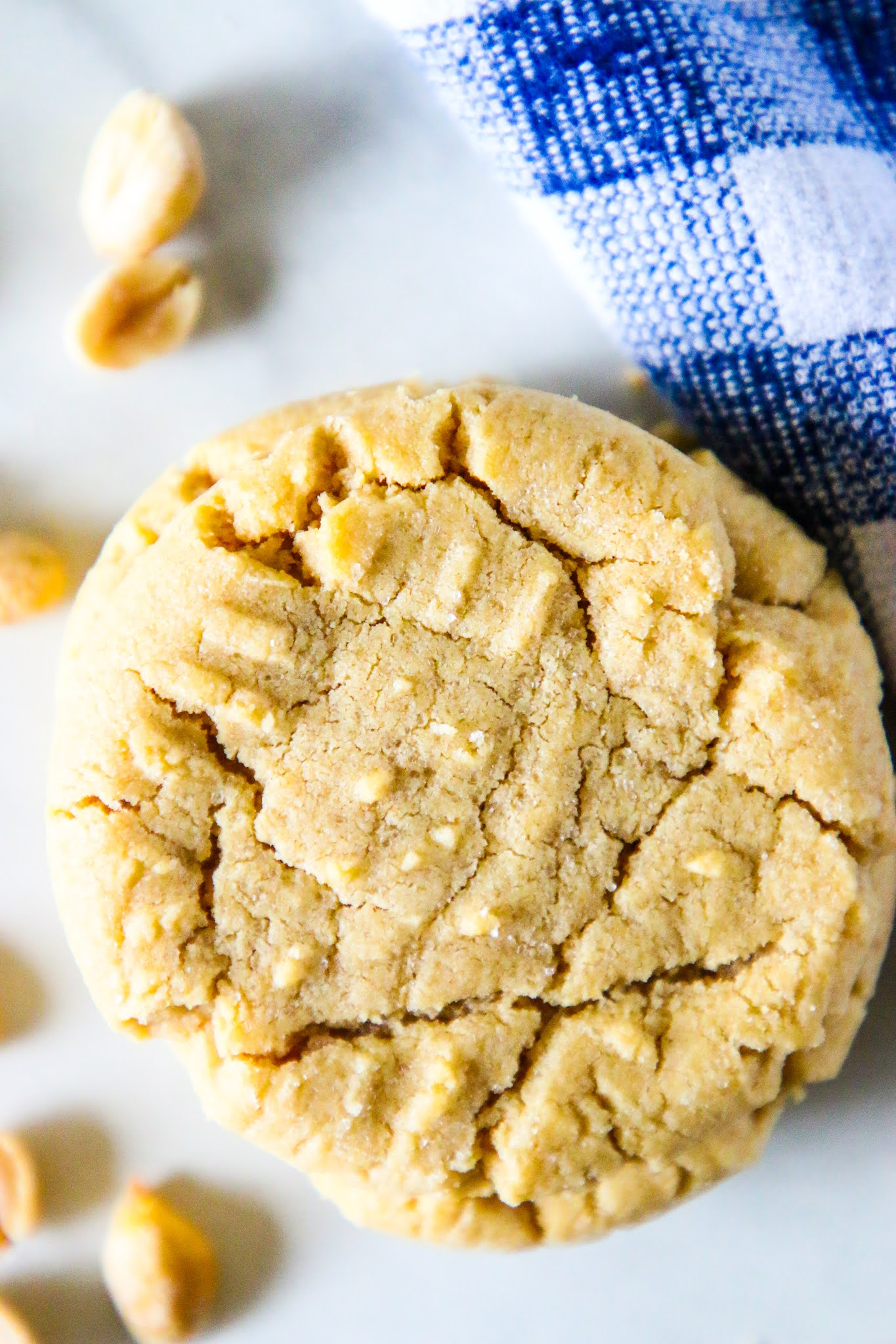 Peanut butter cookies on a marble table scattered with small peanuts and a blue dish towel in the background.