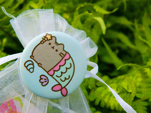 A button badge showing pusheen the cat dressed as a mermaid