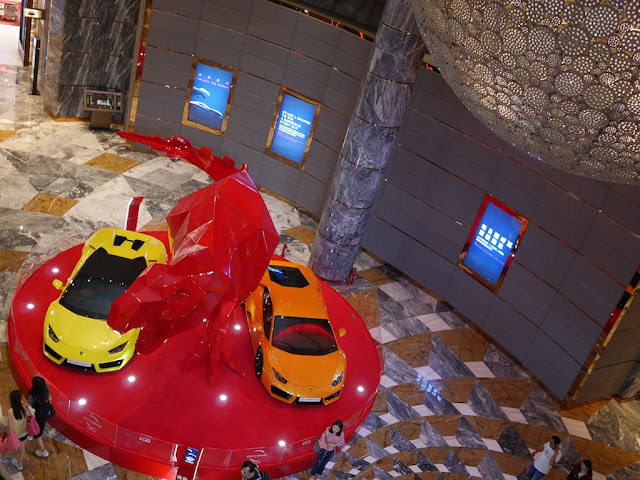view from above of Lamborghinis and Tyrannosaurus sculpture display at City of Dreams Macau