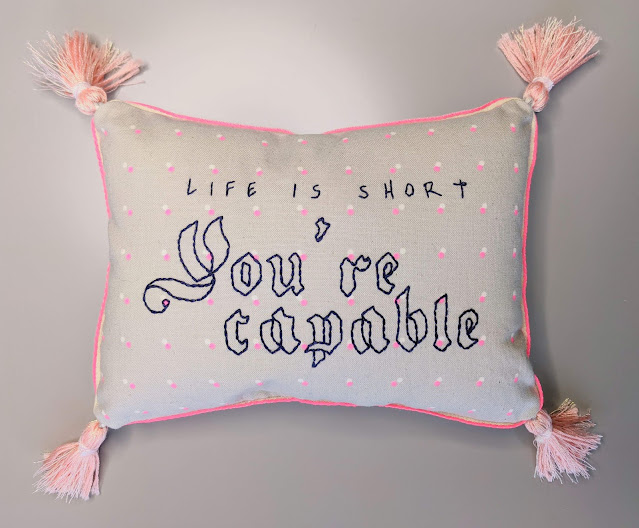 Life is short You're Capable embroidered on decorative pillow with tassels in the corners of the pillow