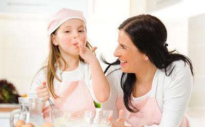 حيل وطرق مفيدة لتخفيف وتقليل إستهلاك عائلتكِ للسكر , طفلة تأكل حلويات ام الامومة تضحك امرأة بنت صغيرة