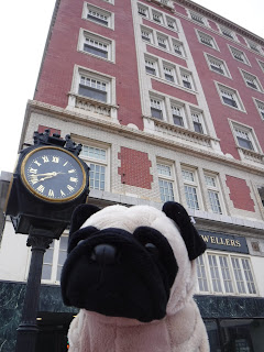 "a black and gold clock stands outside a tall brick building. a sign is partially obscured by a plush pug but reads ""wellers"""