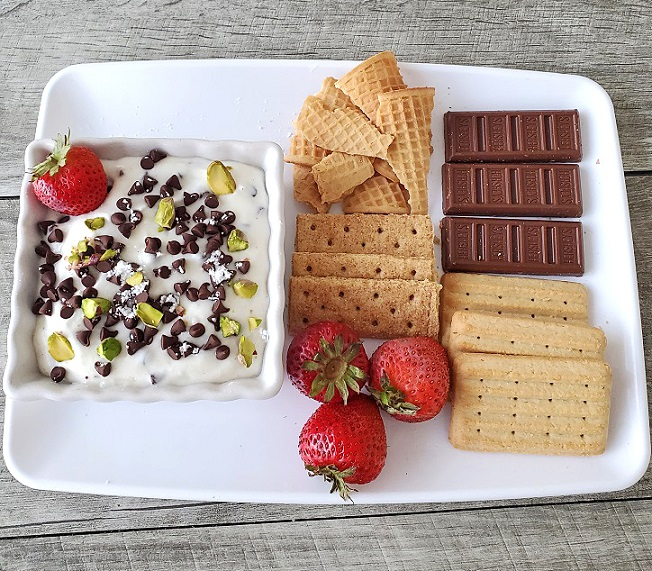 classic Italian Cannoli dessert gets turned into a quick and easy Cannoli Dip with assorted things on the plate to use to scoop it with