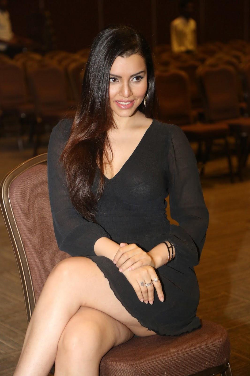 Kyra Dutt in black mini frock skirt sitting crossed legs on a chair