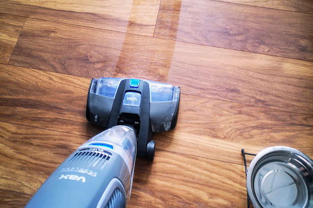 Image of the VAX ONEPWR Hard Floor Cleaner being used in wash mode on a dark oak laminate floor with a dog bowl just in shot.