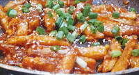 Honey chilli potato recipe topped with green scallions and white sesame seeds