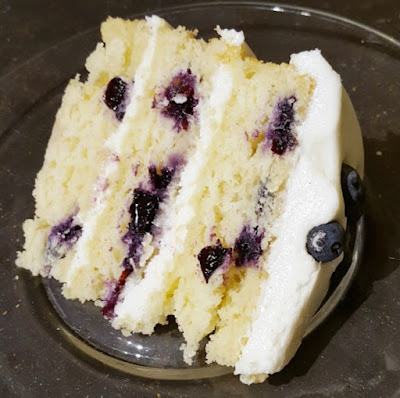 closeup slice of cake with blueberries in cake and lemon frosting between layers