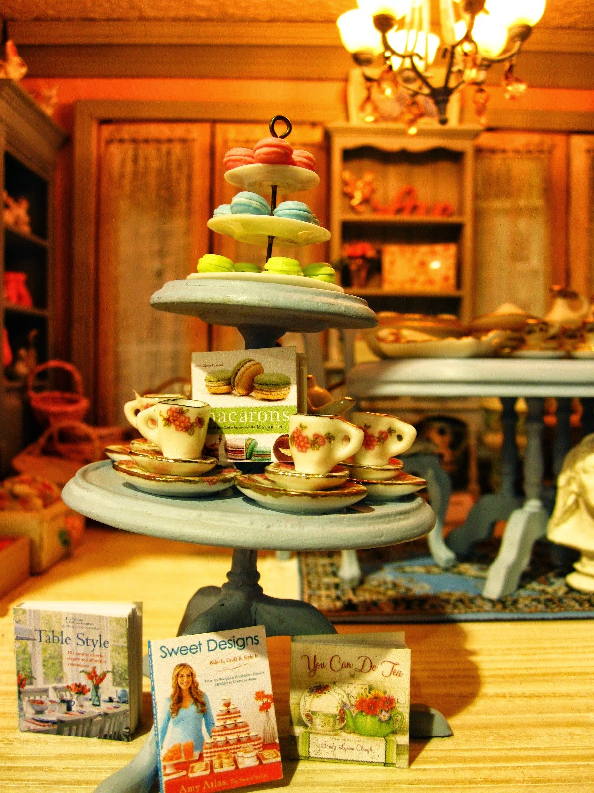 Modern miniature shabby chic shop three tier display of macarons, tea cup sets and cook books.