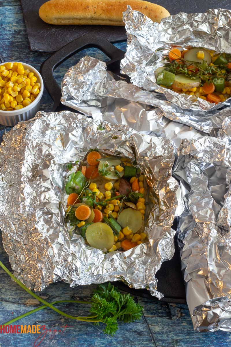 Opened packets of fish in foil with veggies