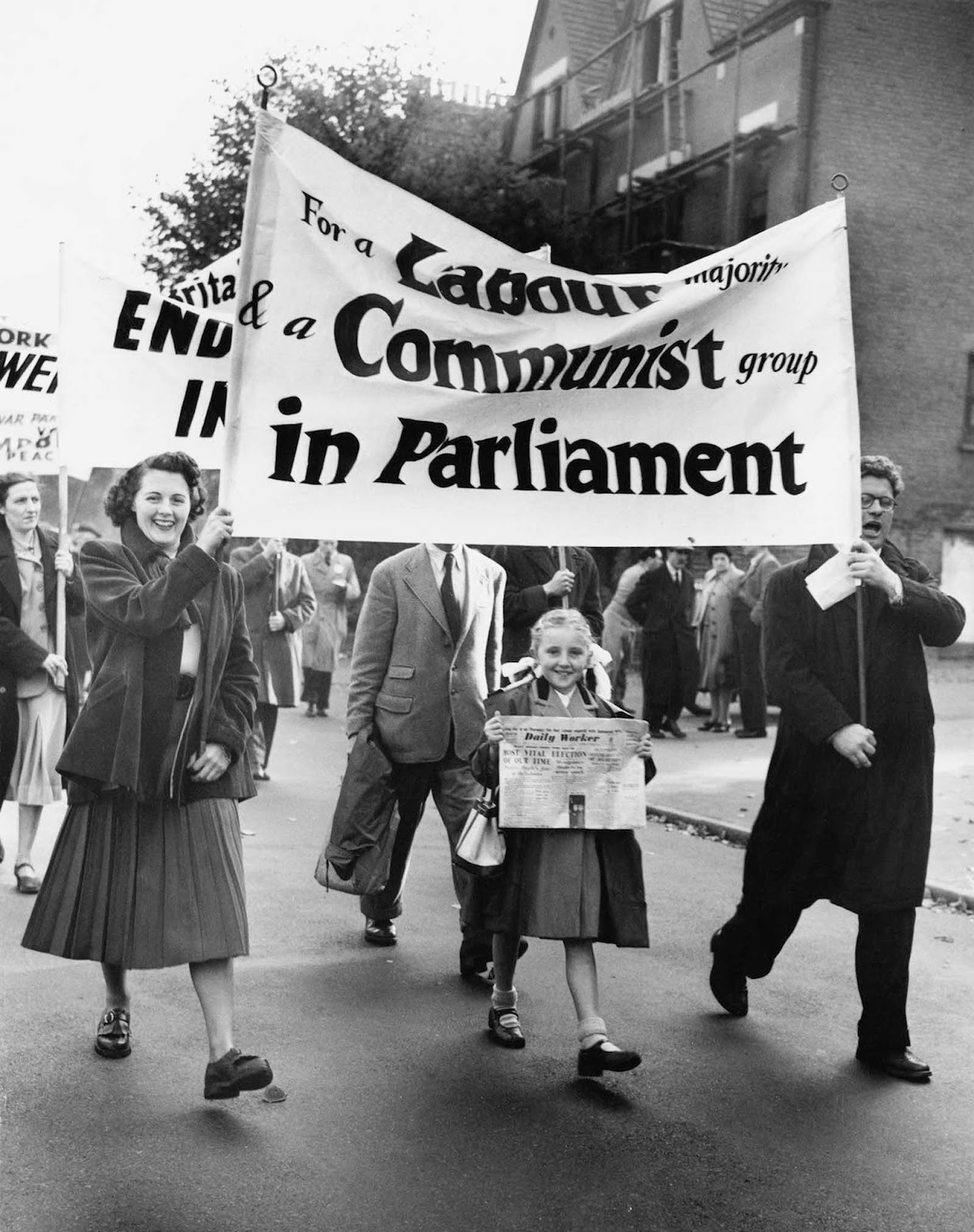Supporters of Communist candidate J. R. Campbell marching through Woodford in Essex in the run-up to the general election, Campbell is up against Conservative candidate Winston Churchill. The girl at the front is holding a copy of 'The Daily Worker'. 1951