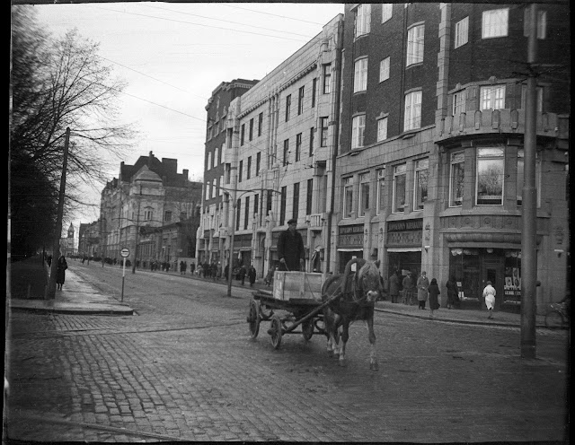 Mustavalkoinen kuva. Kuvassa kaupunkinäkymä kadunristeyksestä. Mukulakivetyksellä astelee hevonen kärryä vetäen.