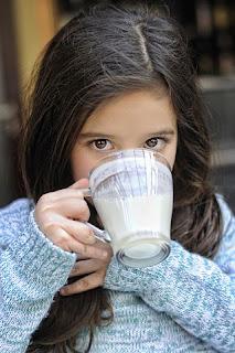 Gadis kecil sedang minum susu
