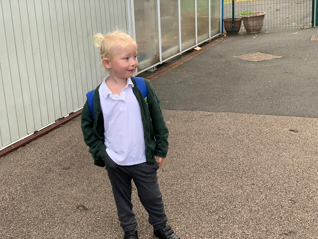 A 3 year old in grey trousers, white t-shirt and green cardigan