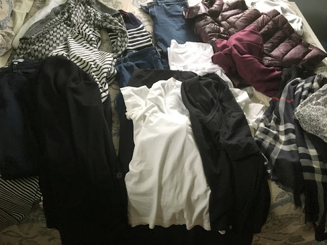 a pile of clothes on a bed