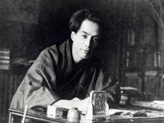 Foto de Akutagawa Ryûnosuke de joven, vestido de la forma tradicional nipona con un kimono y pero recogido, escribiendo en una mesa. Imagen a blanco y negro.