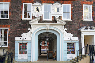 The ground and first floors of part of a Georgian brick building with sash windows. In the centre is an alley passing through the building, with a stucco frontage including a split pediment and scrolls painted white, and a light blue-painted frontage with two windows displaying law books.