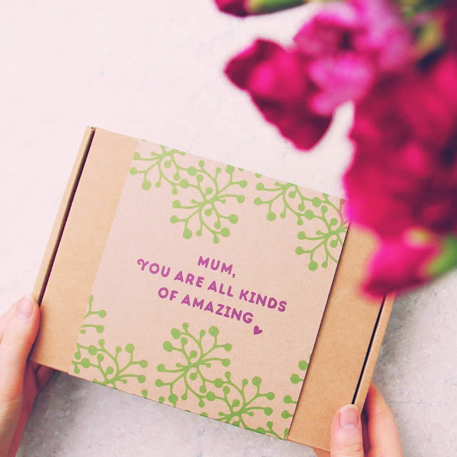 "A cardboard box being held in hands as a gift with the message ""Mum, you are all kinds of amazing"" on it"