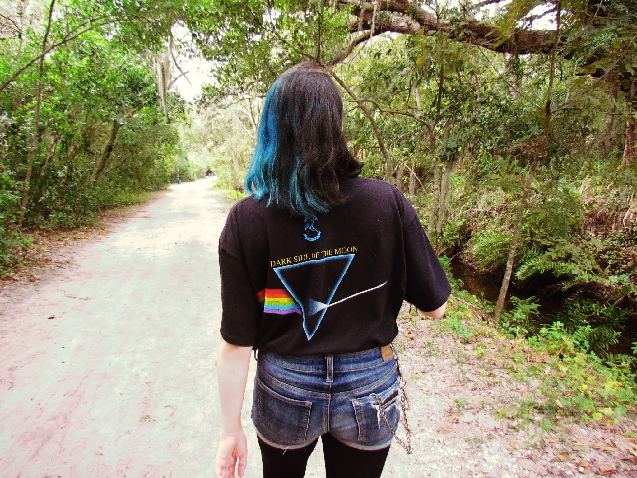 A young girl with blue mermaid hair in the forest on a cool autumn day with a Pink Floyd tee shirt