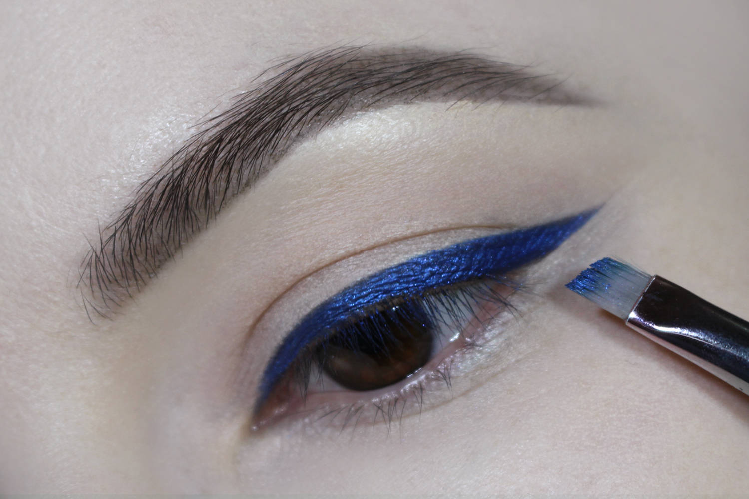 a close-up picture of an eye with a navy-blue cat eyeliner