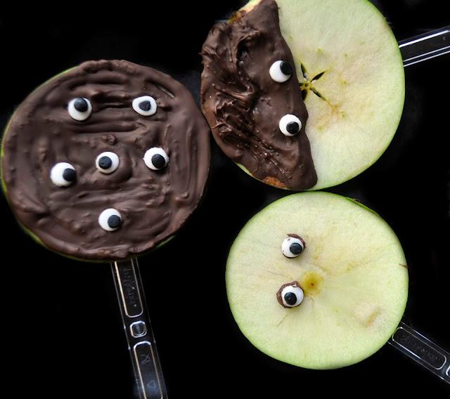 rodajas de manzana cubiertas de chocolate y con ojos de fondant muchos ojos