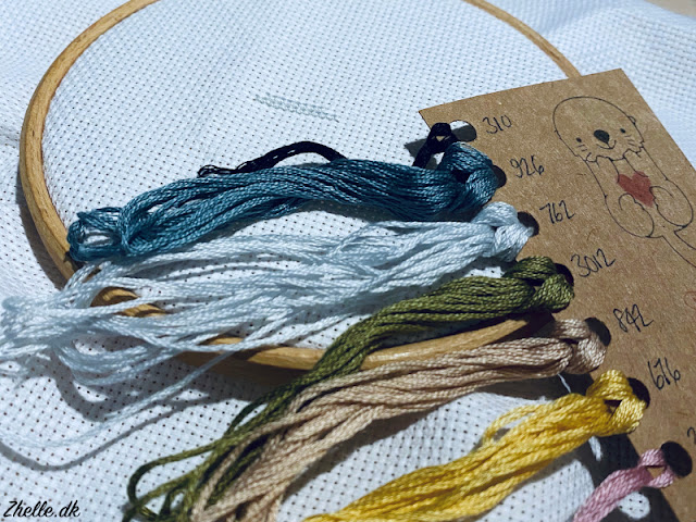 A picture of thread, hoop and fabric from a cross stitch kit