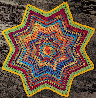 Crochet baby blanket in granny stitch star pattern, rainbow colours in middle with border of pink, green and yellow.