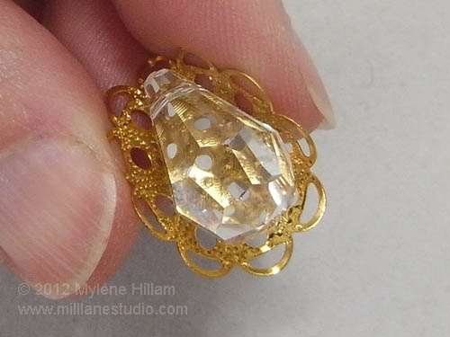 Gently curving the round gold filigree around the crystal briolette