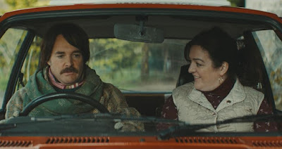 "Christian Winter (Will Forte) sits in the passenger side of Rose Dooley's (Maeve Higgins) car for a driving lesson in the movie ""Extra Ordinary"" (2019)"
